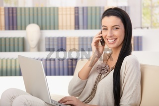 Laughing woman with laptop on call