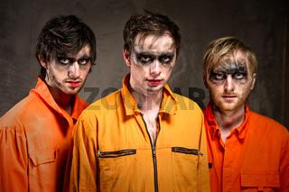 Three criminals in orange uniforms