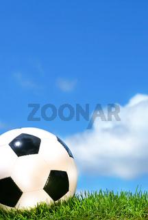 Closeup of a soccerball against a blue sky