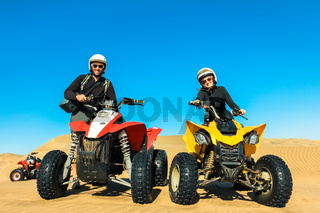 Quad driving people - happy smiling couple bikers in sand desert.