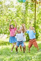 Gruppe Kinder spielt mit einer Weltkugel