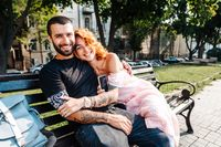 Beautiful dating couple hugging on a bench