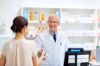 apothecary taking customer credit card at pharmacy
