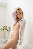 Naked blonde with long locks in luxurious interior