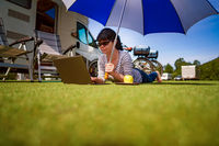 Woman on the grass, looking at the laptop under umbrella near the campe.