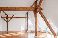 empty loft room with wooden framework and parquet floor
