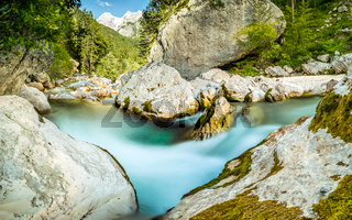 Natural wild river with turquoise water rapids in forest mountain valley.