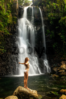 Young woman in bikini standing by Middle Tavoro Waterfalls in Bouma National Heritage Park, Taveuni Island, Fiji
