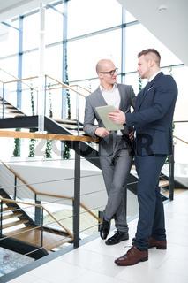 Zwei Berater mit Tablet diskutieren im Treppenhaus