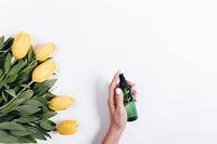 Female hand holds a green plastic bottle of water near yellow tulips, top view