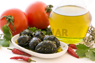 Olives, tomatoes chili and olive oil as closeup on white background