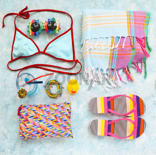 Girls beach accessories and cocktail on turquoise background