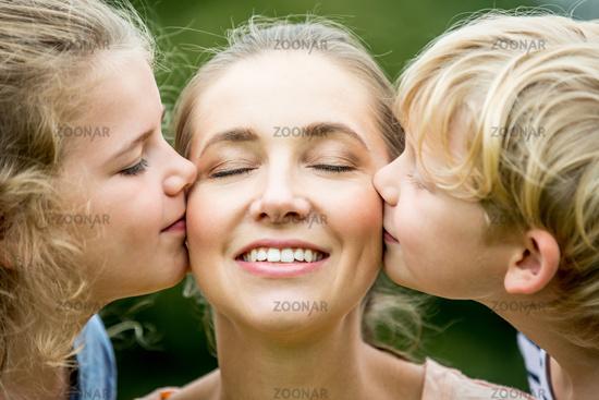 Mutter wird von ihren Kinder geküsst