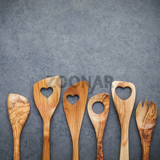 Various wooden cooking utensils border. Wooden spoons and wooden spatula on dark stone background with flat lay and copy space.