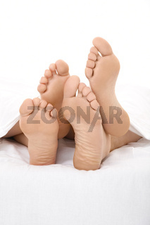 Pair heels are visible under a white bed-sheet