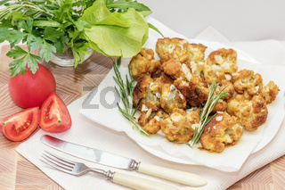 Fried cauliflower in batter on a white plate with white napkin. Close-up