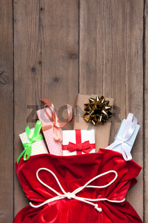 Santa Claus Bag Full By Present Gift Box, Red Christmas Sack on Old Wood Wall Background