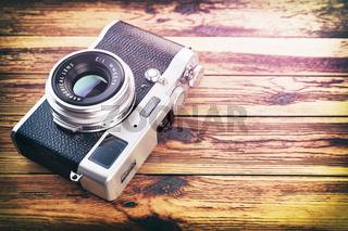 Retro vintage camera on wood table background.