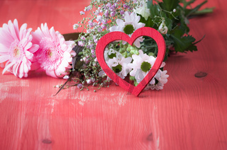 Red heart leaned on flowers