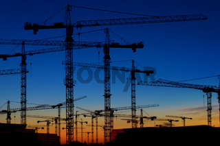 many construction cranes on sunset sky , crane silhouette skyline