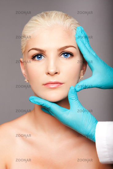 Cosmetic plastic surgeon touching aesthetics face