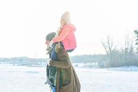 Vater mit Kind auf den Schultern im Winter