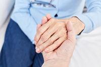 Pflegehilfe hält die Hand einer Seniorin