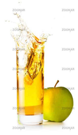 orange juice is spalsing in glass