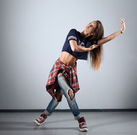 modern young beautiful dancer posing on a studio background