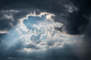 sun rays shining through dark clouds after strom