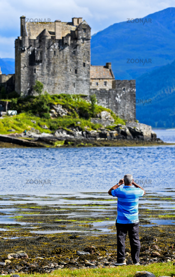 Man taking photos of Eilean Donan Castle, Scotland, United Kingdom