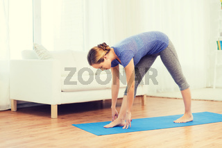 woman making yoga intense stretch pose on mat