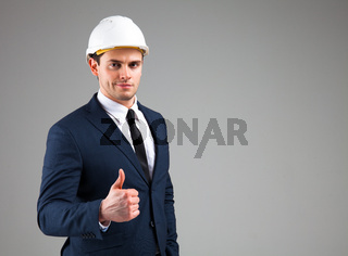 Portrait of a businessman in white helmet on gray background