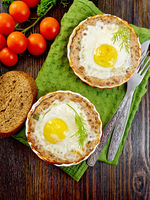 Tartlet meat with egg in pan on board top