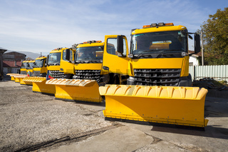 Yellow snowplow trucks in line