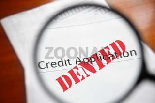 magnifying glass and a Denied credit application form