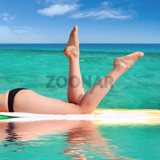 sexy female legs against the turquoise sea background