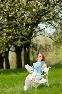 Young woman relaxing under blossom tree in spring