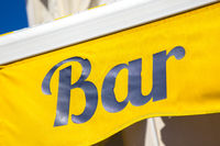 Sign on yellow background with letters saying Bar in blue