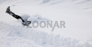 Man is falling headfirst into deep snow. Concept of winterly slippery conditions.