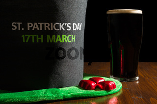 Closeup of St Patrick day with a pint of black beer and hat over a table