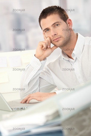 Troubled businessman sitting at desk