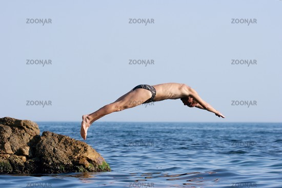 Man jumping headlong into the see