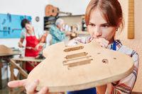 Lehrling fertigt eine neue Gitarre an