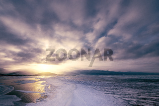 Frozen surface of Baikal lake at sunset.