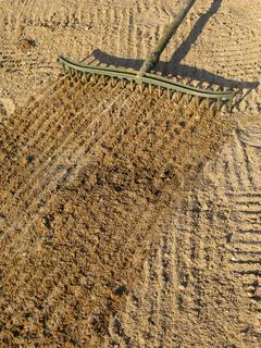 Raking sand with a bunker trap rake.
