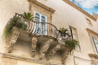 Balcony with baroque decorations in a house of Syracuse (Sicily)