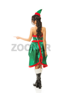 Back view of woman wearing elf clothes pointing to the left