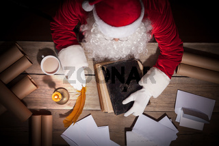 Santa Claus sitting at the table in his room and working
