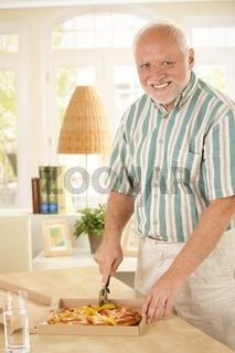 Smiling senior man cutting up pizza
